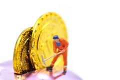 Miniature people : worker digging on gold coins. Miniature people : worker digging on gold coins royalty free stock photography