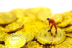 Miniature people : worker digging on gold coins. Miniature people : worker digging on gold coins royalty free stock image