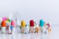 Miniature people: Worker are painting color on medicinal capsules. Image use for Mechanisms of drug production, Healthcare concept Stock Photos