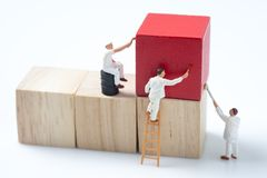 Miniature people worker painting wood cube building block.  Royalty Free Stock Photo