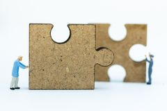 Miniature people : Worker pushing back jigsaw puzzle pieces . Image use for solve, finding solution, business vision concept.  Royalty Free Stock Photo
