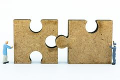 Miniature people : Worker pushing back jigsaw puzzle pieces . Image use for solve, finding solution, business vision concept.  Stock Photos