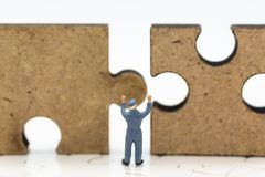 Miniature people : Worker pushing back jigsaw puzzle pieces . Image use for solve, finding solution, business vision concept.  royalty free stock photos