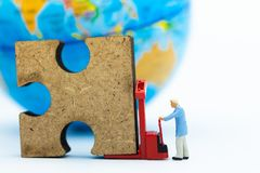 Miniature people : Worker pushing jigsaw puzzle pieces by truck pallet . Image use for solve, finding solution, business vision. Concept Stock Photography