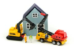Miniature people : worker team for building home ,Image use for construction, business concept,house repair or home renovating.  stock images