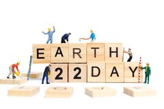 Miniature people : Worker team building word ` Earth day ` on wooden block. With wooden background , Earth day concept Royalty Free Stock Photos