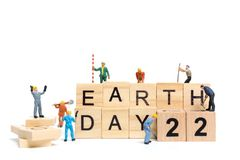 Miniature people : Worker team building word ` Earth day ` on wooden block. With wooden background , Earth day concept Stock Photos