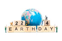 Miniature people : Worker team building word ` Earth day ` on wooden block. With wooden background , Earth day concept Stock Image
