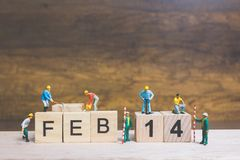 Miniature people : Worker team building word ` 14 FEB ` on wooden block. With wooden background , Valentine`s day concept Stock Images