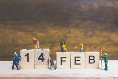 Miniature people : Worker team building word ` 14 FEB ` on wooden block. With wooden background , Valentine`s day concept Stock Photo