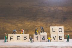 Miniature people : Worker team building word ` 14 FEB ` on wooden block. With wooden background , Valentine`s day concept Royalty Free Stock Image