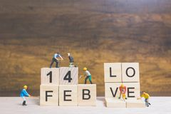 Miniature people : Worker team building word ` 14 FEB ` on wooden block. With wooden background , Valentine`s day concept Royalty Free Stock Photography