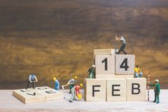 Miniature people : Worker team building word ` 14 FEB ` on wooden block. With wooden background , Valentine`s day concept Royalty Free Stock Images