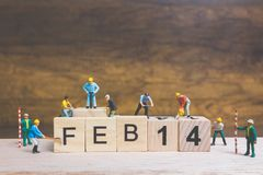 Miniature people : Worker team building word ` 14 FEB ` on wooden block. With wooden background , Valentine`s day concept Royalty Free Stock Photo
