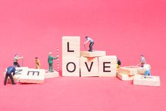 Miniature people : Worker team building word ` Love ` Stock Photography
