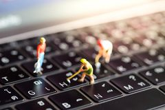 Miniature people : worker team with button on a computer keyboa stock images