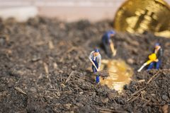 Miniature people : Worker team digging ground to uncover big shi. Ny bitcoin ,  Successful work concept Royalty Free Stock Photo