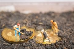 Miniature people : Worker team digging ground to uncover big shi. Ny bitcoin ,  Successful work concept Royalty Free Stock Images