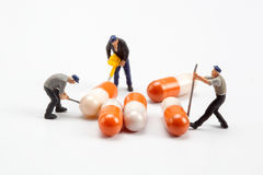 Miniature people  - workers moving capsules pills Royalty Free Stock Photos