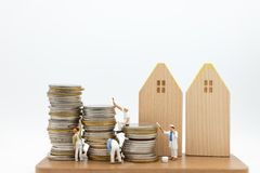 Miniature people: Workers are painting color on the coins. Image use for saving money, business concept royalty free stock photography