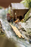 Miniature people: workers on sawmill at the river. Macro photo, shallow DOF. Stock Photo