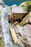 Miniature people: workers on sawmill at the river. Macro photo, shallow DOF. Royalty Free Stock Photo