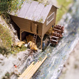 Miniature people: workers on sawmill at the river. Macro photo, shallow DOF. Stock Image