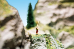 Miniature people: young man playing long trumpet in the mountains. Adventure, travel, tourism, hike and eco nature concept. Stock Photography