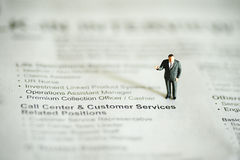 Miniature peoples business man on news paper Stock Photo