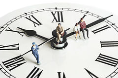 Miniature peoples on clock Royalty Free Stock Images