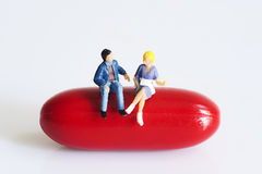 Miniature peoples on red capsule Stock Images