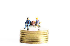 Miniature peoples sit on coins Stock Photography