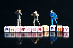 Miniature Photographers taking pictures behind a Group Of Letters forming Word Spelling. `Photography` on a black glass surface with mirror image royalty free stock photo