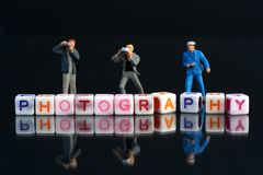Miniature Photographers taking pictures behind a Group Of Letters forming Word Spelling. `Photography` on a black glass surface with mirror image royalty free stock photos