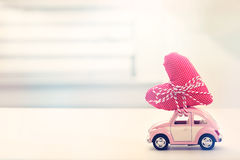 Miniature pink car carrying heart cushion. Miniature pink car carrying a heart cushion royalty free stock photography