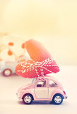 Miniature pink car carrying heart cushion. Miniature cars carrying a polka dots heart cushion stock image