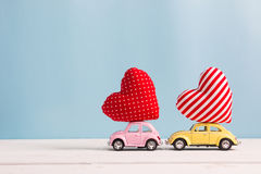 Miniature pink and yellow cars carrying heart cushions. Valentines day concept royalty free stock images