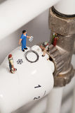Miniature Plumbers Repairing A Thermostat. A team of miniature toy plumbers repiar a thermostat in a career and employment concept Stock Images