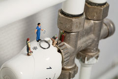 Miniature Plumbers Repairing A Thermostat. A team of miniature toy plumbers repiar a thermostat in a career and employment concept Stock Image