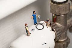 Miniature Plumbers Repairing A Thermostat. A team of miniature toy plumbers repiar a thermostat in a career and employment concept Stock Photo