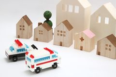 Police car and ambulance heading to hospital on white background. Miniature police car and ambulance heading to hospital on white background stock photos