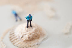 Miniature policeman on a stack of sand while one is lying dead i Stock Photography