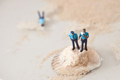 Miniature policeman on a stack of sand while one is lying dead i Stock Photos