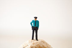 Miniature policeman on a stack of sand Stock Photos