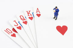 Miniature policeman standing on the gamble card Stock Images