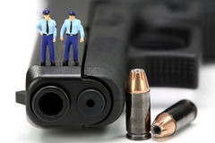 Miniature policemen standing on a gun. Stock Images