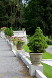 Miniature potted trees and flowers lining stone walkway of landscaped garden Royalty Free Stock Photos