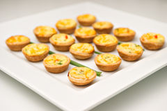 Miniature quiches on a white plate Stock Photo