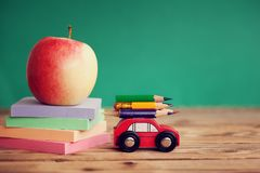 Miniature Red Car Carrying a colorful pencils and red apple and stack papers on wooden table. Back to school concept.  stock photos