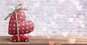 Miniature Red Car Carrying Heart Stock Photo